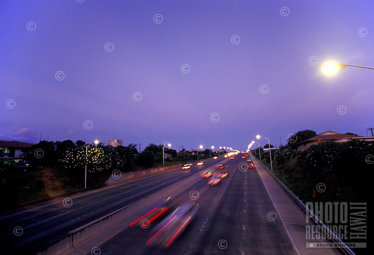 Cars rush by at sunset on H1 freeway near Koko Head Blvd, Honolulu, Hawaii
