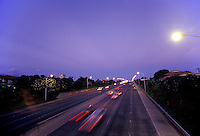 Cars rush by at sunset on H1 freeway near Koko Head Blvd, Honolulu, Hawaii