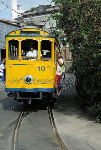 Bonde, Rio's famous electric tram at the stopLargo do Guimaraes; Rio de Janeiro, Espirito Santo, Brazil. The historic street railway has been transporting Rio residents for over a century. The little yellow tram rattles along the track like an antique roller coaster. Starting from downtown Carioca Station across the Arcos da Lapa (a former aqueduct) it is riding through the neighborhood of Santa Teresa. Seating is on wooden benches, but the local daredevils prefer swinging from the tram's outer poles. --- No releases available.
