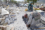 Following an October 8, 2005, earthquake, a woman in Balakot watches as rescuers dig into the rubble of her house, which collapsed on several family members inside.