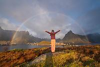 Female stands below circular rainbow with hands raised, Reine, Lofoten Islands, Norway