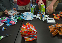NWA Democrat-Gazette/CHARLIE KAIJO Items are displayed on a table on Sunday, November 12, 2017 at the Circle of Life Hospice meeting room in Bentonville. Ninth and tenth grade boys from the Ozark Chapter of Young Men's Service League created care packages to send to a troop of 50 soldiers stationed in Kandahar, Afghanistan. Immediately prior to the service project, they heard firsthand experiences from a military veteran who was stationed in Kandahar.