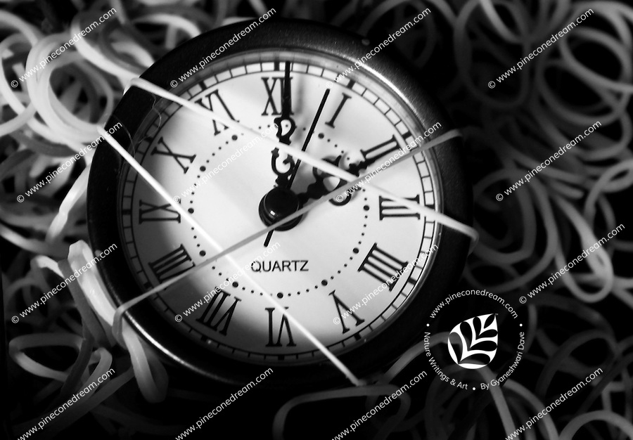 Artistic black & white stock image of a small clock with roman numbers wrapped and surrounded by rubber-bands.<br />