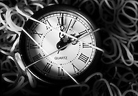 Artistic black &amp; white stock image of a small clock with roman numbers wrapped and surrounded by rubber-bands.<br />