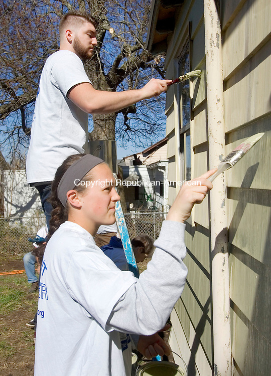 WATREBURY CT. 02 May 2015-050215SV08-Devon Gancher and Katherine Flaherty both of Watertown paint a house at 38 Ayers St. in Waterbury Saturday. Volunteers from HomeFront were rehabbing the home of Bill Carroll as part of a campaign to revitalize 70 homes of low-income families. These volunteers were from St. Mary Magdelene Church in Oakville. <br /> Steven Valenti Republican-American