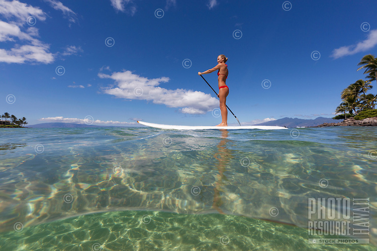 Water level view of a woman standup paddling at Napili Bay, Maui.