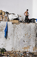 A Moroccan boy lives in an improvised shack built on the wall of the the Tanger port, Morocco, 21 January 2007. Every day tens of Moroccan young men try to cross ilegally the Strait of Gibraltar. ?Harraga? (immigrants in Arabic) come to Tanger from all over Morocco. They try their good luck and hidden between the wheels of a truck they attempt to board on a ferry and get to Spain, eventually further to Europe. Considering the thorough checks at the port only few of them make it. Therefore they spend months living on a beach, in huts along the walls of the port, begging for food and waiting for the right night so as their dream about Europe came true.