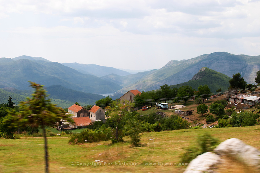A panoramic view across the tremendously impressive Orin or Bijela Gora mountain tops close to the border to Montenegro on the road between Trebinje and Niksic. View of a small village along the road. Trebinje region. Republika Srpska. Bosnia Herzegovina, Europe.