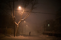 A person walks through the streets in Huron Village in Cambridge, Massachusetts, USA, as Winter Storm Nemo approaches on Friday, Feb. 8, 2013.
