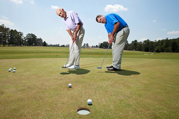 June 24, 2010. Pinehurst, North Carolina..Eric Alpenfels, a golf coach at Pinehurst, and Dr. Bob Christina, a former dean at UNC-Greensboro, have developed a theory that putting is more successful when the player looks at the hole rather than the ball while hitting their shot.. Bob Christina, left, and Eric Alpenfels putt on the practice green of the Pinehurst Golf Resort..