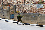 An IDF soldier throws a concussion grenade at Palestinian youths (unseen) throwing rocks following a nonviolent demonstration against Israel's controversial separation barrier in the West Bank town of Beit Jala near Bethlehem on 27/06/2010.