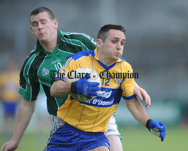 Clare's Brian Curtin pushes past Limerick's John O' Connell. Photograph by Declan Monaghan