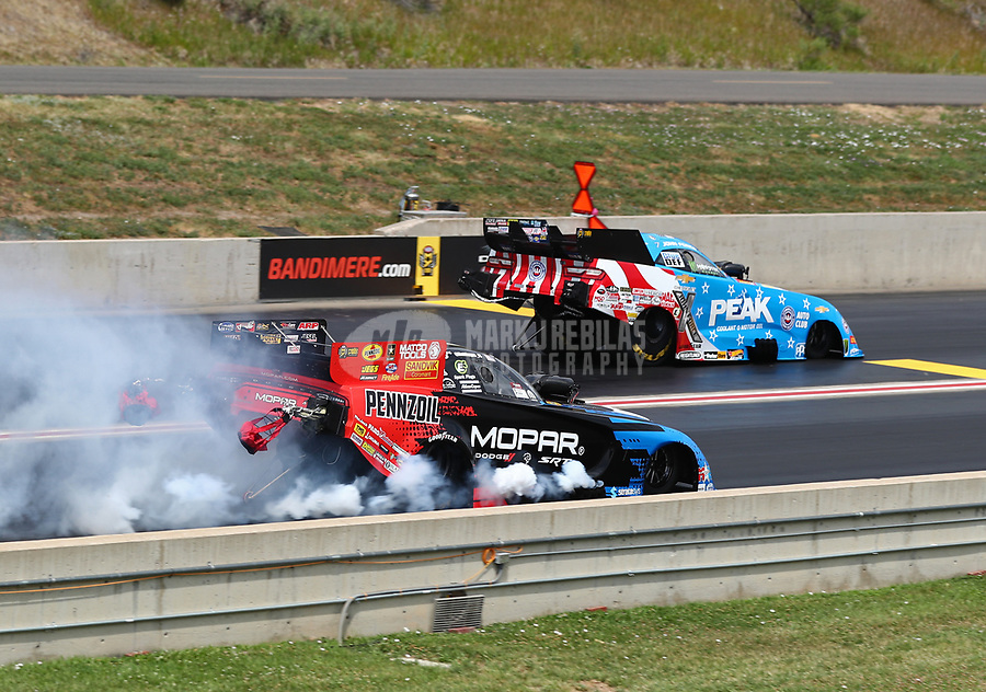 Jul 22, 2018; Morrison, CO, USA; NHRA funny car driver Matt Hagan (near) is defeated by John Force during the Mile High Nationals at Bandimere Speedway. Mandatory Credit: Mark J. Rebilas-USA TODAY Sports