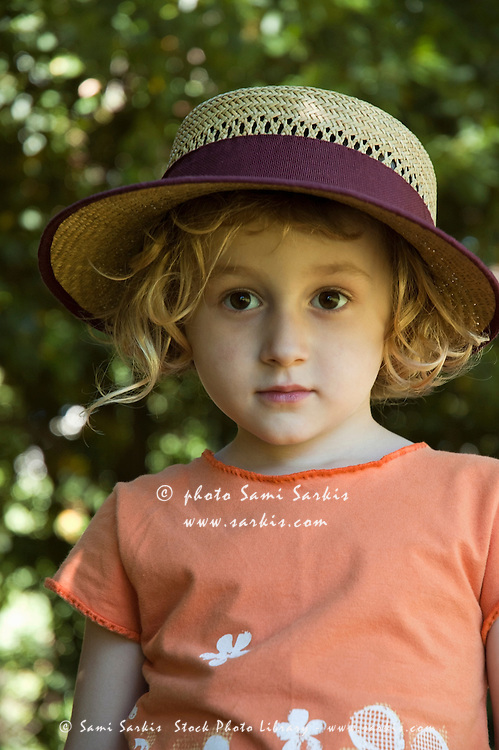 Little girl wearing a straw hat, Provence, France.