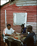 This is the village at the gate of the St. Louis Cardinals camp. The locals played dominoes, cook sphagetti dinner and sold food by the side of the road. They have no running water inside their homes. Cooking is done outside on a fire. ..The Saint Louis Cardinals maintain a baseball training camp in the Dominican Republic near  Villa Mella, just outside the capital. The players from all around Latin American are playing for a chance to go to Spring Training in Jupiter, Florida. They range in age from 16-22yrs old.