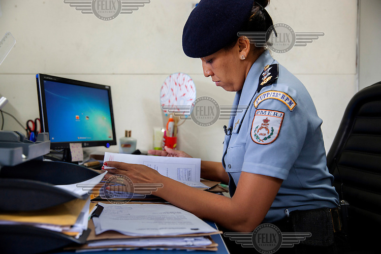 Major Priscilla (L) working at her desk. The major commands the Rocinha UPP (Police Pacification Unit). The pacification policy aims to reduce violence in favelas and rest control from drug gangs.