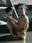 A mother baths her child in a klong. People live on the klongs, boulevards of water that flow through the city like open veins,  and spend their lifetimes living in houseboats in Bangkok, Thailand. (Jim Bryant Photo).....