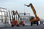 HARDINXVELD GIESSENDAM - In Hardinxveld-Giessendam worden door Duitse bouwvakkers in opdracht van Rijkswaterstaat, glazen panelen gemonteerd die onderdeel zijn van een lange geluidswand. ruimt een sloopbedrijf de laatste resten op van de toerit van een oud boogviaduct over snelweg A15. De werkzaamheden zijn onderdeel van de verbreding van de snelweg A15 die voorlopig nog het meeste, en zwaarste vrachtwagenverkeer van Nederland te verduren krijgt. Naast een verbreding van de snelweg worden gelijktijdig viaducten vernieuwd en op- en afritten gewijzigd. ANP PHOTO COPYRIGHT TON BORSBOOM