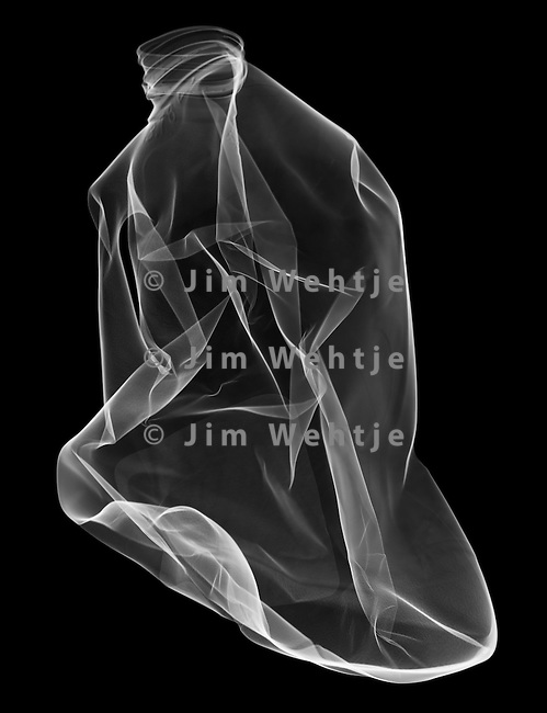 X-ray image of a crushed milk jug (white on black) by Jim Wehtje, specialist in x-ray art and design images.