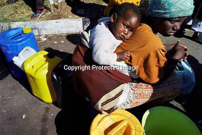 An unidentified mother and baby wait in a long paraffin queue on June 27, 2000 in Harare, Zimbabwe. Due to the deteriorating economic situation, people use paraffin for cooking. Zimbabwe has suffered a severe economic downturn the last few years due to President Robert Mugabe and his policies. (Photo by: Per-Anders Pettersson)