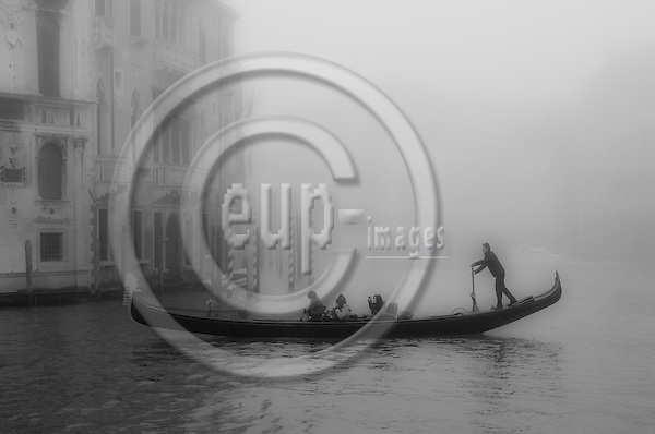 Venice-Italy - January 16, 2011 -- A gondoliere / gondolier on tour with tourists on Grand Canal / Canal Grande in the early morning winter mist, gondola -- tourism, infrastructure, transport, water, b&w -- Photo: Horst Wagner / eup-images