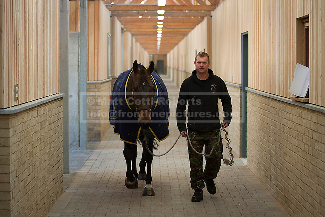 07/02/2012. LONDON, UK. A member of the King's Troop Royal Horse Artillery leads a horse through new purpose built and carbon neutral barracks in Woolwich. Previously based at St John's Wood since 1947, the Royal Artillery's ceremonial unit today arrived at their new home at Napier Barracks in Woolwich Photo credit: Matt Cetti-Roberts