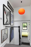 A bold pendant light and modern art add interest to the white walls of the stairwell