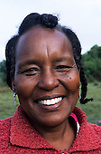 Lolgorian, Kenya. Portrait of a smiling African woman, Priscilla, with silver earrings and plaited hair.