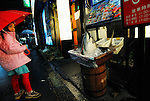 A young girl looks at the the severed head of a tuna placed outside a restaurant specializing in tuna cuisine in Tokyo, Japan on Friday March 13 2009.