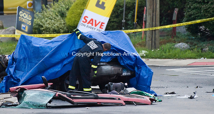 WATERBURY, CT-080217JS02-- A Waterbury fire department investigator, looks under the tarp, covering one of the cars involved in a two-car collision on Homer Avenue in Waterbury on Wednesday night. Two people, one from each car, died in the accident. <br />  Jim Shannon Republican-American