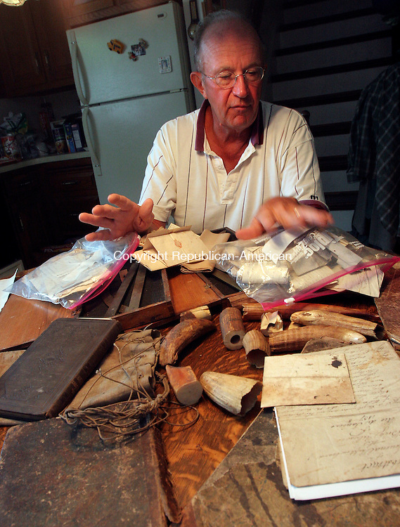 BRISTOL, CT-07August 2006-080706TK01- Dick Blaschke of Bristol inspects 1830 whaling journals and memorabilia from the same era. The items were discovered in the attic of a Cheshire home that will be auctioned off on August 12. The journals and letters belong to a George Elliot, a first mate on whaling ships sailing out of Connecticut ports. Tom Kabelka Republican-American (Dick Blaschke)
