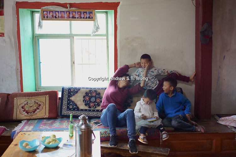 Diqing Tibetan Autonomous Prefecture, Yunnan Province, China - Members of a Tibetan family play underneath portraits of Communist leaders, August 2018.
