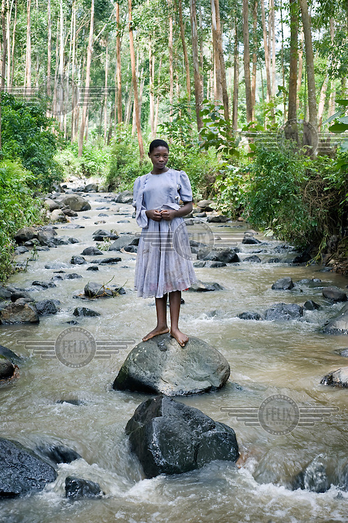 13 year old Rita Nabugibi stands on a rock in the river in the local forest.