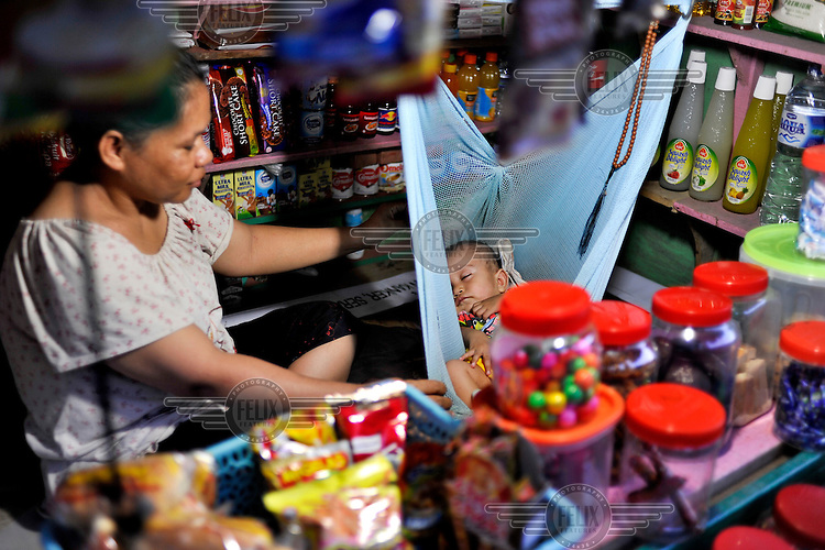 Snack stall owner rocks her baby in a makeshift cradle inside the store. The 1999-2002 religious war between Maluku's Christian and Muslim populations, mainly centred on Ambon Island, led to over 5000 deaths and to around 500,000 people become displaced. Destroyed homes and offices, churches and mosques are slowly being either torn-down or renovated.  Urban centres, such as Ambon City, continue to be split along largely sectarian lines, and tensions are never far below the surface. Riots between Christian and Muslim youths erupted in September 2011 and, most recently, June 2012, though luckily simmered down just as quickly, partly due to community leaders learning how to defuse tensions from the earlier, more devastating, conflagration. /Felix Features