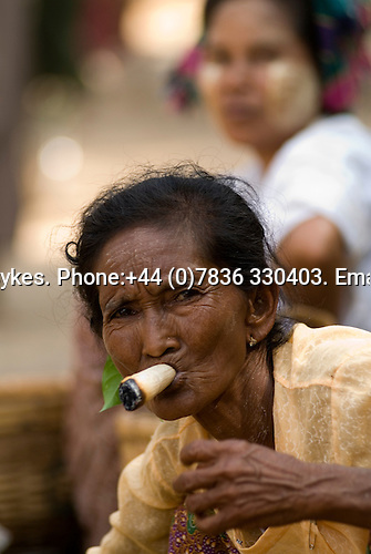 Older woman smoking a huge roll your own cigar at Nyaung-U market Bagan, Myanmar (Burma.) 2006