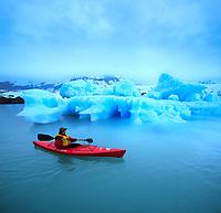 Kayaking around floating iceberg in Nellie Juan Lagoon, Prince William Sound, Alaska