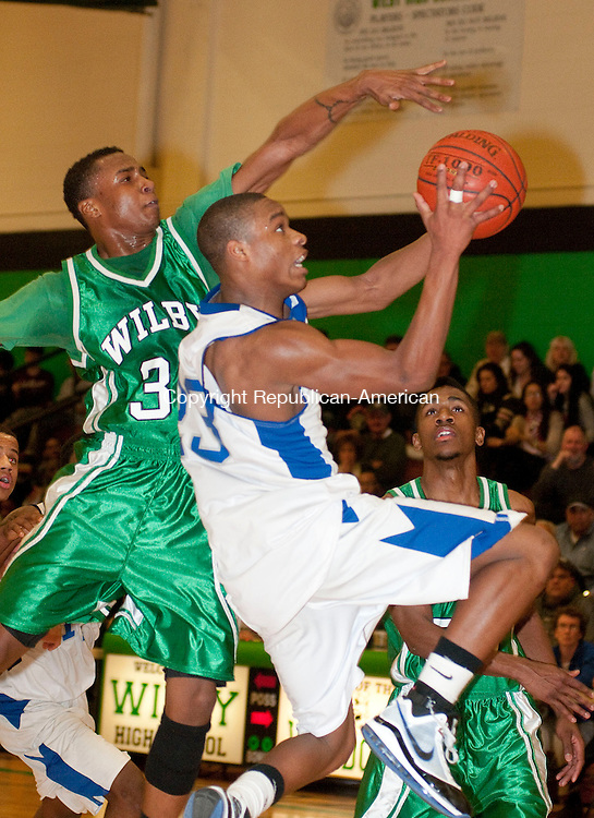 WATERBURY, CT, 28 FEBRUARY 2011-022811JS06--Crosby's Tyshon Rogers (23) lays up a shot under the block attempt by Wilby's Marcus Robinson (31) during their NVL semi-final game Monday at Wilby High School in Waterbury. <br /> Jim Shannon/Republican-American