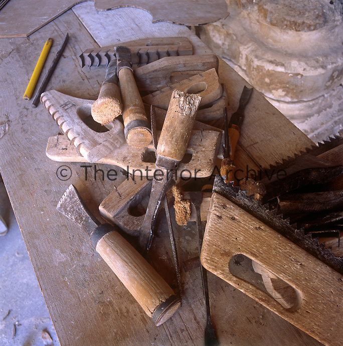 A selection of carpentry and joinery tools are laying on a work bench.