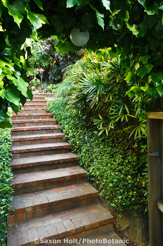 Brick path steps leading up hill inside entry gate to Worth garden, California
