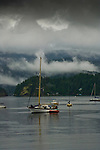 Yacht in Deep Cove Bay with clouds above the mountains and forests  over Mount Seymour provincial park. Deep Cove, Burrard Inlet, Vancouver, British Columbia, Canada.
