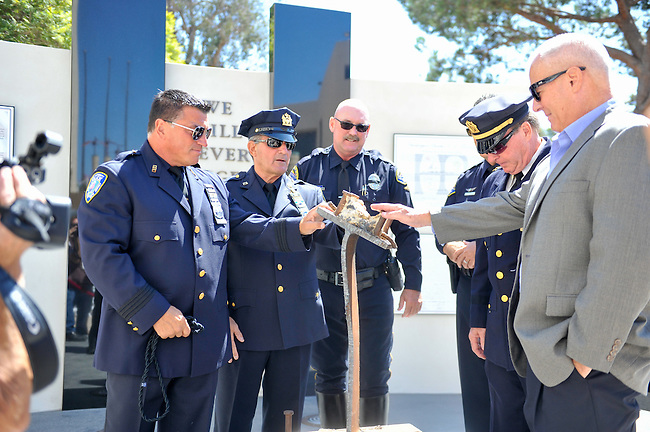 Officers from the New York Port Authority, (left to right) Vincent Zappulla, Jr, Frank Accardi, Huntington Police Officer, Corwin Bales, New York Port Authority Officer, Kevin Devlin and Robert Egbert surround the unveiled 9/11 Memorial at Huntington Beach City Hall before the ceremony on Sunday afternoon.<br /> <br /> ///ADDITIONAL INFORMATION: hb.0915.memorial – 9/11/16 – MICHAEL KITADA, ORANGE COUNTY REGISTER - _DSC8496.jpg - <br /> Summary: The Huntington Beach Police Officers' Foundation's 9-11 Memorial Committee unveils a $200,000 monument including steel from the toppled World Trade Center, at City Hall. The event will include music, a flyover, New York police and others with connections to the 9-11 rescue and victims of the tragedy.