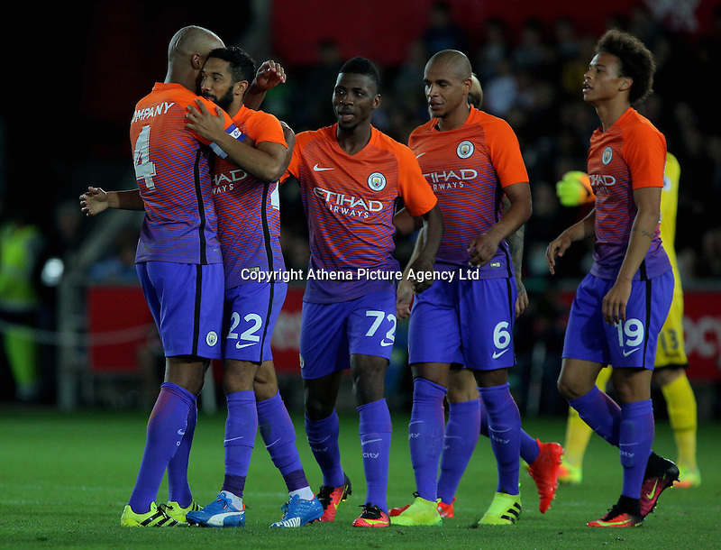 Dael Clichy of Manchester City (2nd L) celebrates his opening goal with team captain Vincent Company (L) and other team mates during the EFL Cup Third Round match between Swansea City and Manchester City at The Liberty Stadium in Swansea, Wales, UK. Wednesday 21 September.
