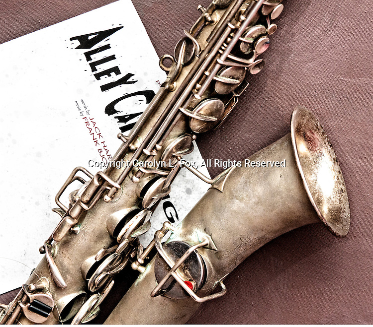 An antique melody c saxophone lays on a mauve background on top of a piece of jazz sheet music.