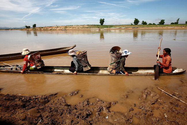 A group of Bahnar women head across a river to work their rice fields near the Central Highlands town of Kon Tum, Vietnam. The Bahnar are one of more than two dozen hill tribes known formerly in the West as Montagnards, but who are now called the Dega. April 14, 2012.