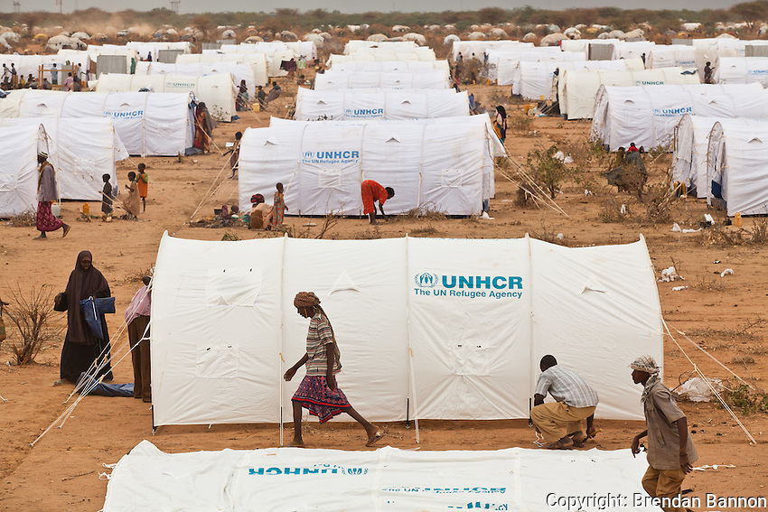 Kenya/ Somali refugees. Workers erect 300 tents per day to accomodate 1,500 people in Ifo camp extension. The  residents of the new tents are being shifted from un-safe areas at the outskirts of the camp. UNHCR/ Brendan Bannon/ July 2011.