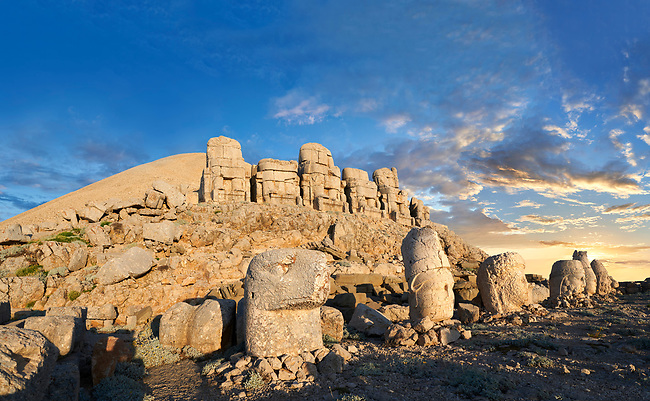 Statue heads at sunset, from left,  Eagle, Antiochus, Commagene, Zeus, Apollo, & Herekles with headless seated statues in front of the stone pyramid 62 BC Royal Tomb of King Antiochus I Theos of Commagene, east Terrace, Mount Nemrut or Nemrud Dagi summit, near Adıyaman, Turkey