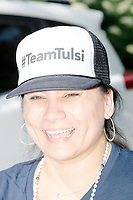 "A supporter of Democratic presidential candidate and Hawaii representative Tulsi Gabbard wears a ""#TeamTulsi"" hat while marching in the 4th of July parade in Amherst, New Hampshire, on Thu., July 4, 2019."