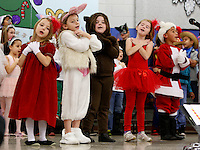 NWA Media/DAVID GOTTSCHALK - 12/16/14 - Ashlyn Harris, left to right, Pearlie Rutledge, Shelby Mason, Catherine Eriksen (cq) and Shawn Swinson, all first grade students at Asbell Elementary School in Fayetteville performs with three first grade classes Tuesday December 16, 2014. The theme of the performance was Miss Popinger's Christmas under the direction of music teacher Carlena Lambert.