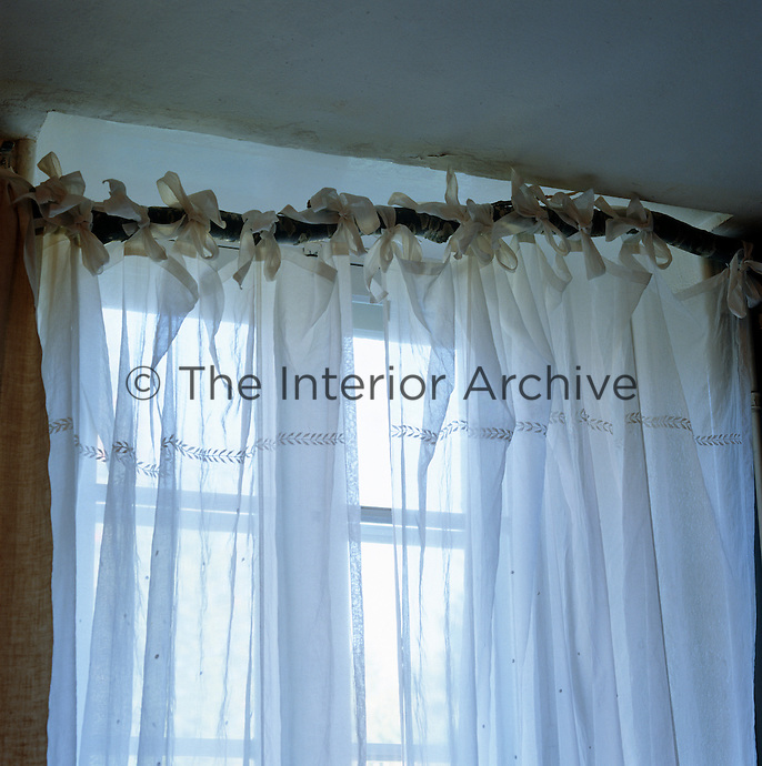 A simple cotton sheer tied to a length of branch in lieu of a curtain pole