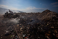 Trash burns alongside rubble dumped by a street west of Port-au-Prince. The 7.0 earthquake that devastated parts of Haiti on January 12 killed hundreds of thousands of people. January's earthquake killed hundreds of thousands of people and caused significant and lasting structural and economic damage in the Caribbean nation.